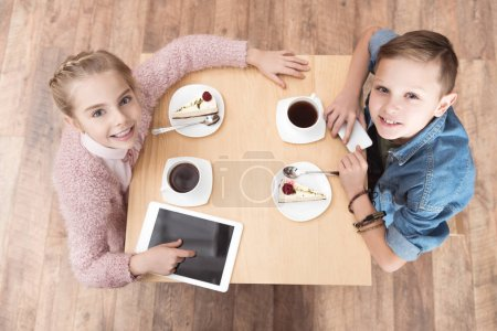kids looking at camera while sitting at table with gadgets on surface at cafe