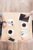 cropped image of kids sitting at table with gadgets on surface at cafe