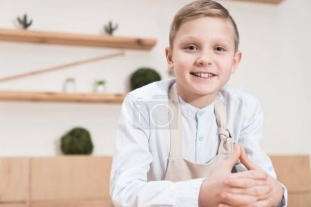 smiling boy in apron looking at camera while leaning on table at cafe