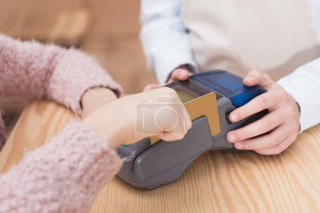 Close up of payment terminal on wooden surface and hands of girl with card