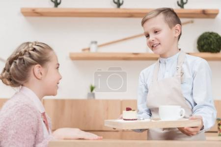 little waiter holding wooden tray in hands with dessert against kid sitting at table at cafe