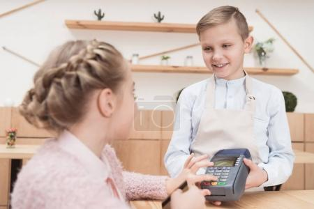 kid paying by credit card with terminal in cafe