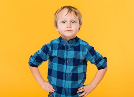 portrait of little boy in shirt standing akimbo isolated on yellow