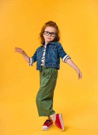 cute little kid in eyeglasses dancing isolated on yellow