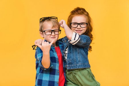 Photo for Portrait of smiling kids in eyeglasses isolated on yellow - Royalty Free Image