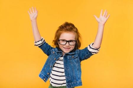 portrait of cute little kid in eyeglasses with outstretched arms isolated on yellow