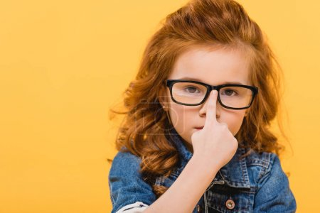 portrait of cute little kid in eyeglasses isolated on yellow