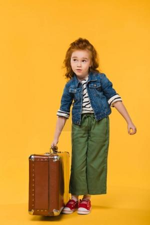 stylish child holding suitcase isolated on yellow