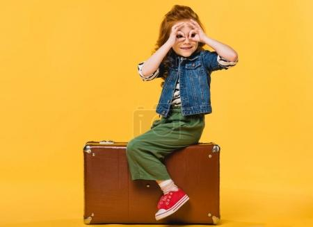 side view of kid sitting in suitcase isolated on yellow