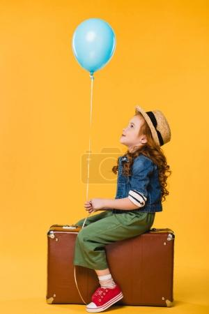 side view of kid with balloon sitting in suitcase isolated on yellow