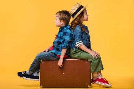 side view of children sitting on leather suitcase isolated on yellow