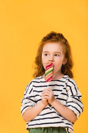 Photo for Portrait of preteen child eating lollipop isolated on yellow - Royalty Free Image