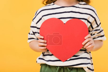 Photo for Partial view of kid with red paper heart in hands isolated on yellow, st valentines day concept - Royalty Free Image
