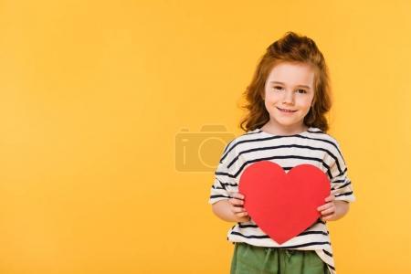 Photo pour Portrait d'un enfant souriant avec coeur en papier rouge isolé sur jaune, concept Saint-Valentin - image libre de droit