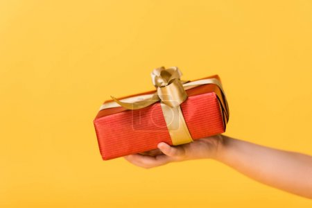 cropped shot of kid holding wrapped gift isolated on yellow