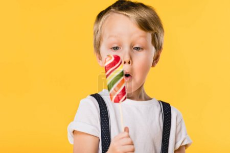 selective focus of adorable little boy with lollipop in hand isolated on yellow