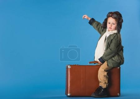 side view of boy in pilot costume sitting on suitcase isolated on blue