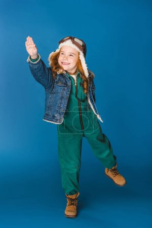 happy adorable preteen kid in pilot costume gesturing isolated on blue