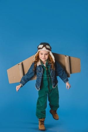 adorable preteen kid in pilot costume with paper plane wings isolated on blue