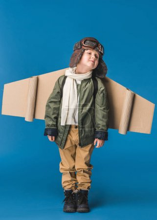 cute little boy in pilot costume with paper plane wing isolated on blue