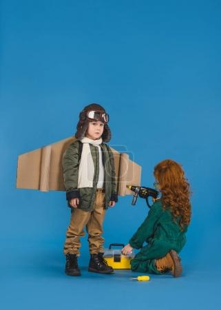 kids in pilot costumes with toy screwdriver playing together isolated on blue