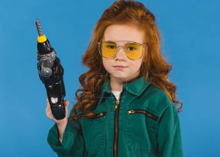 portrait of child in pilot costume with toy screwdriver isolated on blue