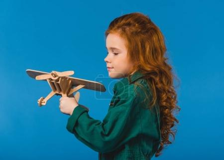 portrait of adorable child in pilot costume with wooden plane toy isolated on blue