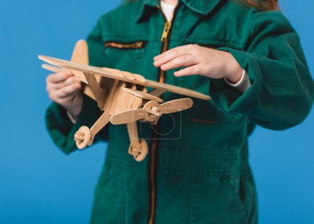 cropped shot of child in pilot costume with wooden plane toy isolated on blue