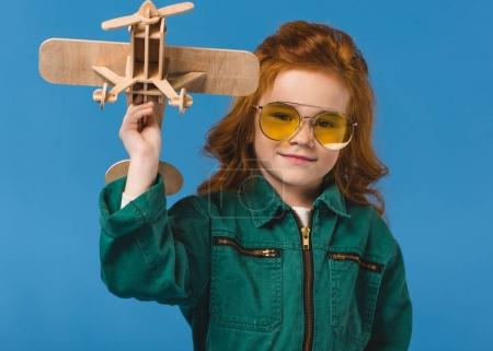 portrait of smiling child in pilot costume with wooden plane toy isolated on blue