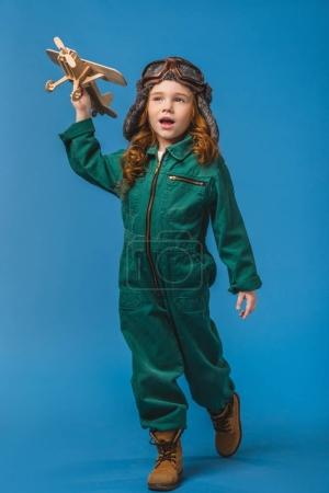 adorable child in pilot costume with wooden plane toy isolated on blue