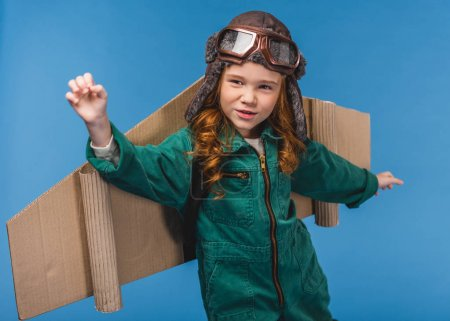 portrait of cute child in pilot costume with handmade paper plane wings isolated on blue
