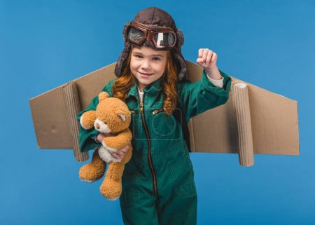 portrait of cute child in pilot costume with teddy bear and handmade paper plane wings isolated on blue