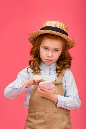 portrait of little child using smartphone isolated on pink
