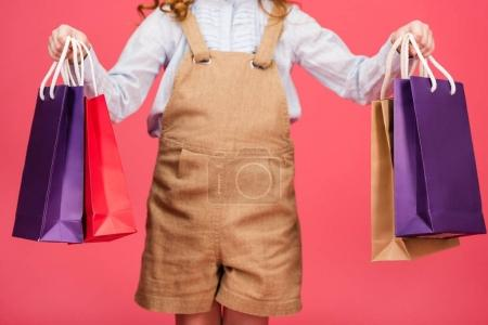 Photo for Cropped shot of kid in casual clothing with shopping bags isolated on pink - Royalty Free Image