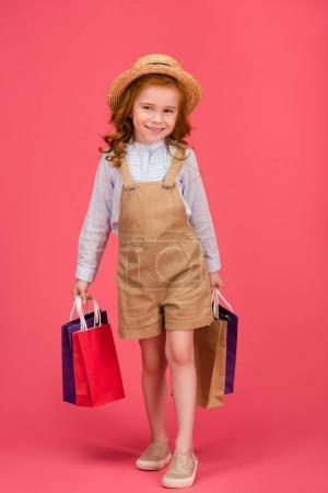 smiling kid in casual clothing with shopping bags isolated on pink