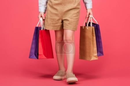 cropped shot of kid in casual clothing with shopping bags isolated on pink