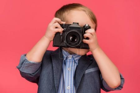 obscured view of kid holding photo camera isolated on pink