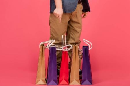 partial view of kid pointing at shopping bags isolated on pink