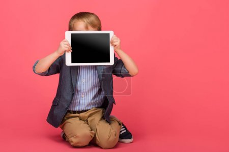 Photo for Little boy covering face with tablet with blank screen isolated on pink - Royalty Free Image