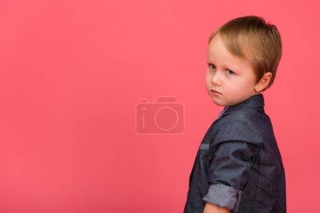 side view of adorable little boy isolated on pink
