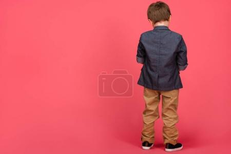back view of boy in casual clothing isolated on pink