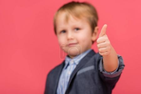 selective focus of little boy showing thumb up isolated in pink