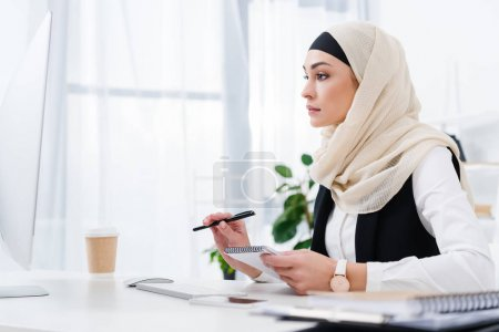 side view of focused arabic businesswoman with notebook sitting at workplace in office