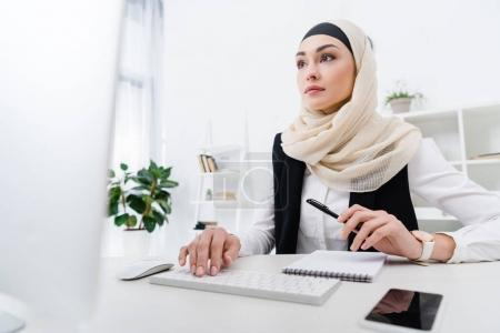 portrait of focused arabic businesswoman working on computer in office