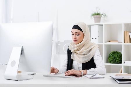 portrait of focused muslim businesswoman working on computer in office