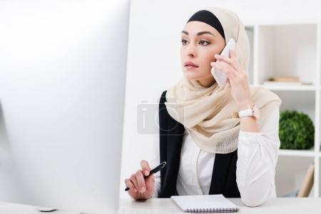 focused businesswoman in hijab talking on smartphone at workplace in office
