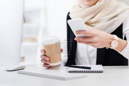 partial view of businesswoman with coffee to go using smartphone at workplace