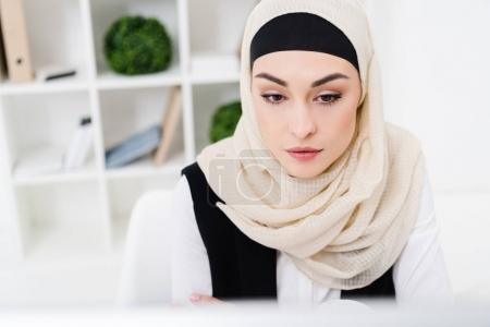 portrait of beautiful pensive businesswoman in hijab in office
