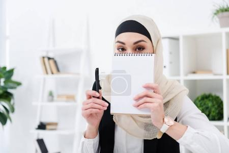 obscured view of arabic businesswoman with empty notebook in office