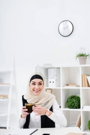 portrait of cheerful muslim businesswoman with cup of coffee at workplace in office